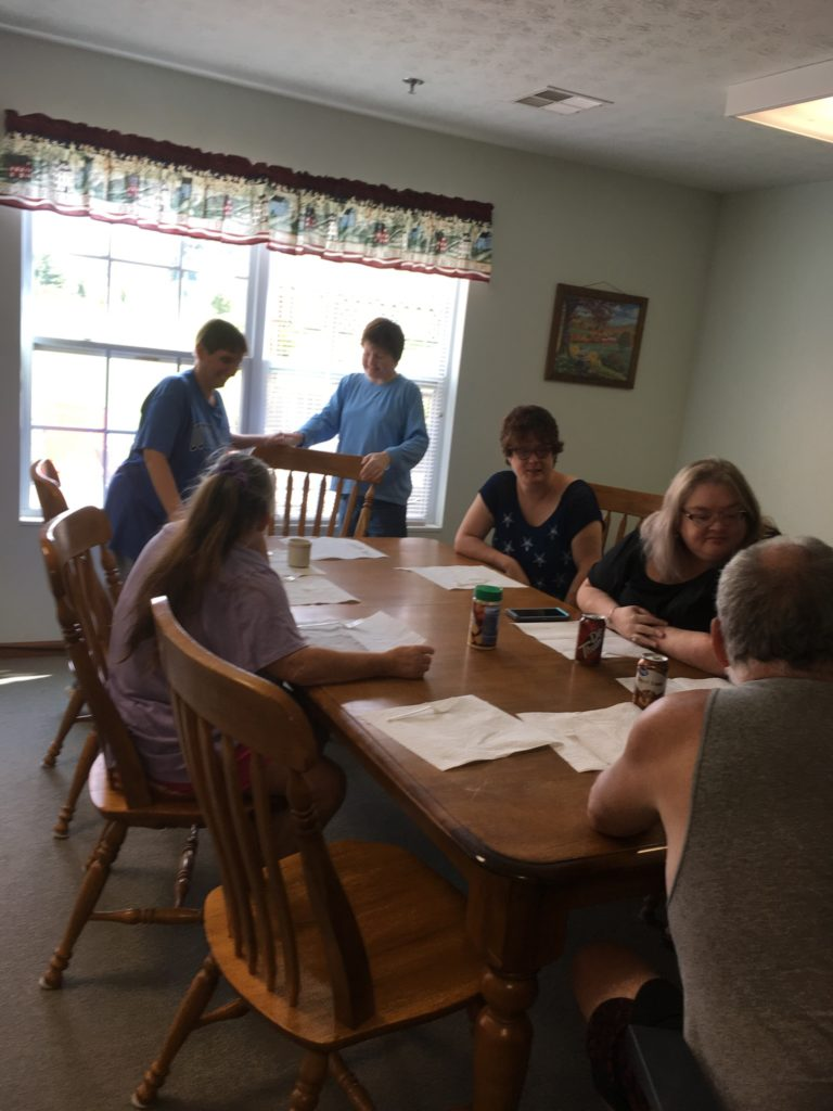 A group of individuals sitting around a table conversing.