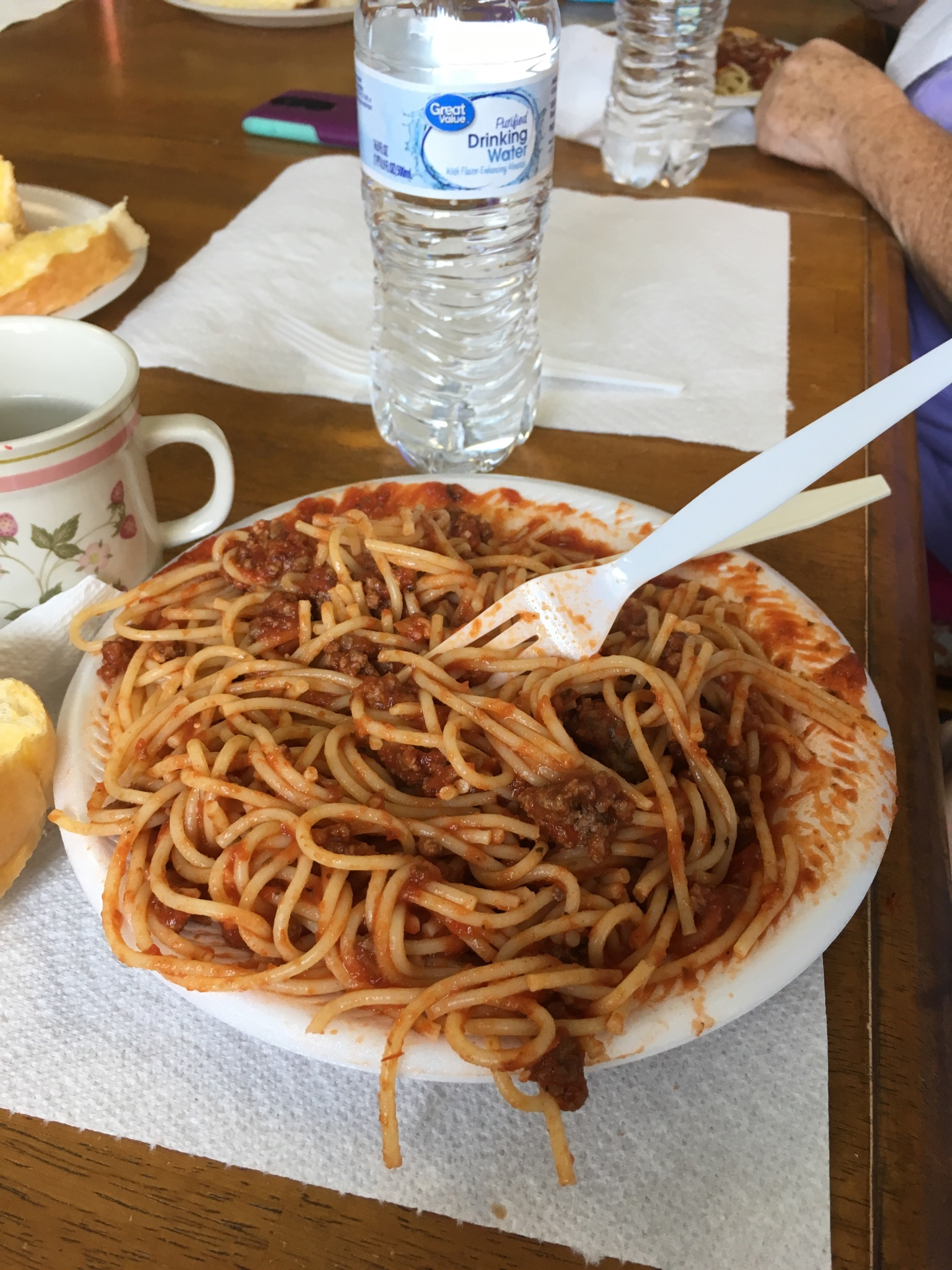 A heaping plate of spaghetti with a bottle of water in the background.