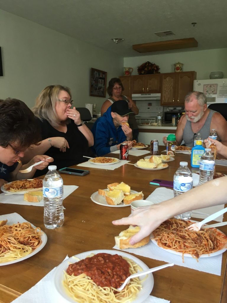 A group of people sitting around a table enjoying spaghetti.