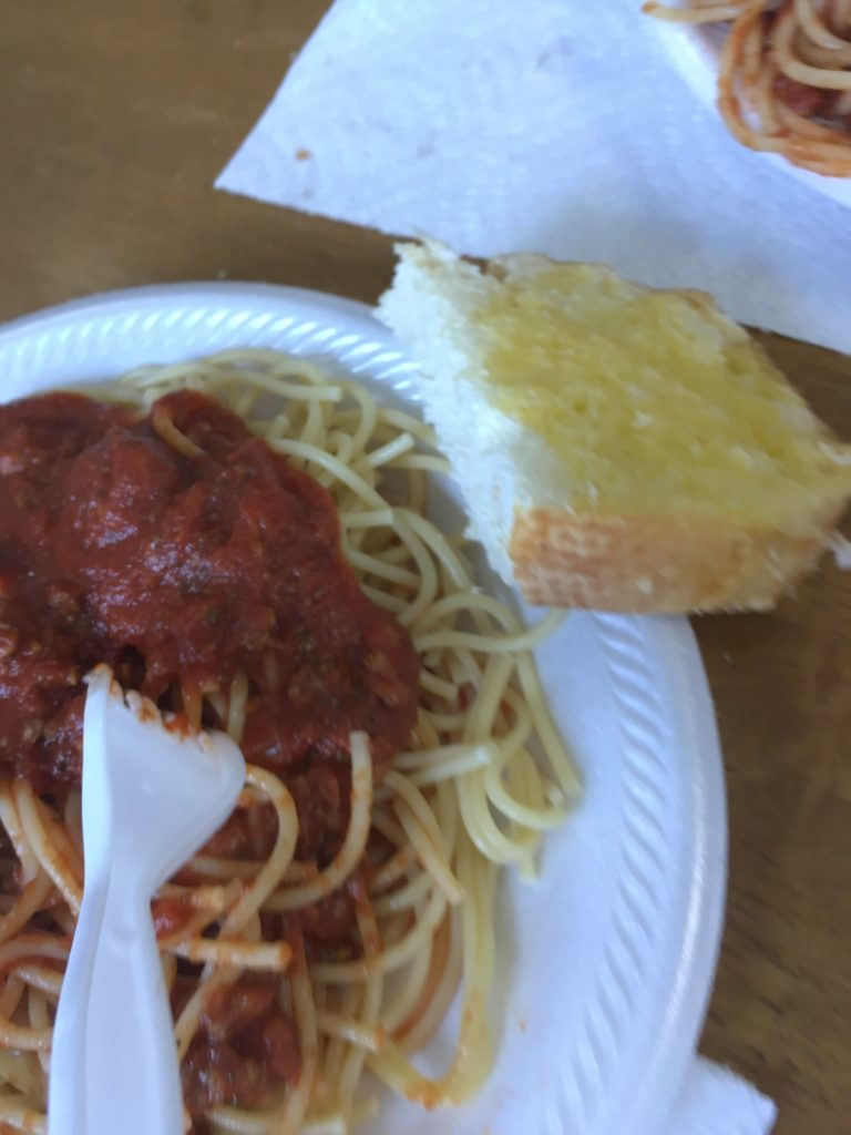 A large plate of spaghetti with a piece of garlic bread on the side.