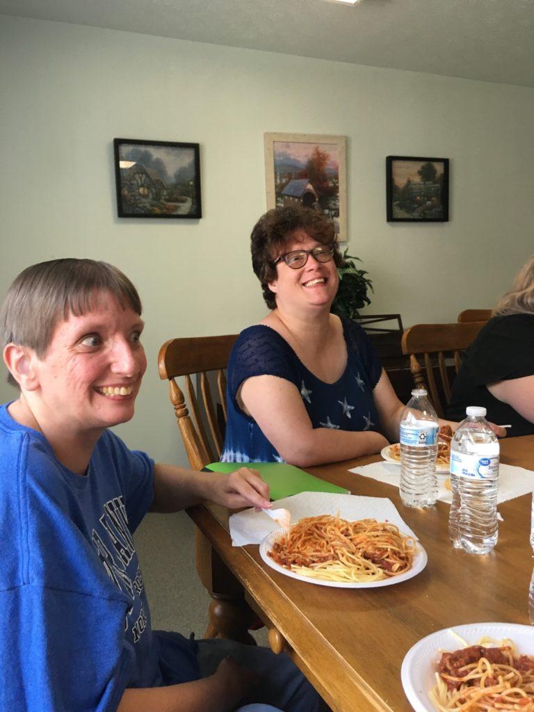 Two people enjoying spaghetti.