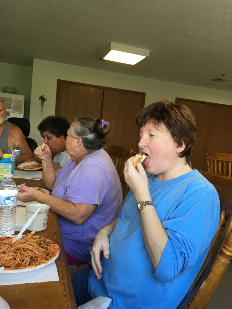 A group of people enjoying spaghetti around a table.