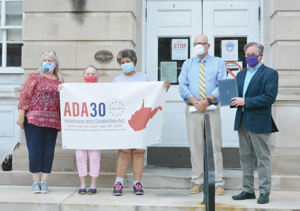 "5 individuals wearing masks holding a sign that says ""ADA 30."""