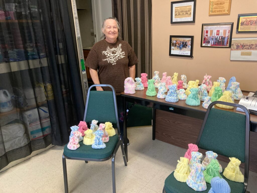 Woman stands next to table filled with crocheted baby hats.